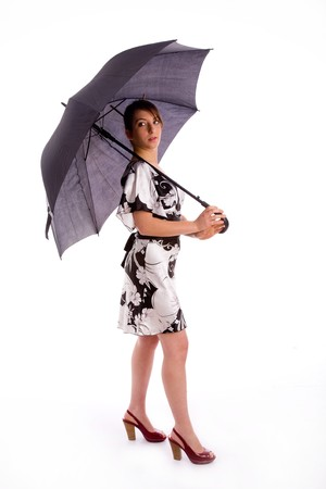 full body pose of young woman holding umbrella against white background photo