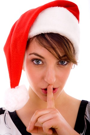 shushing: front view of shushing woman in christmas hat on an isolated white background Stock Photo