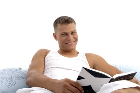 smart male reading book with great interest in bed photo