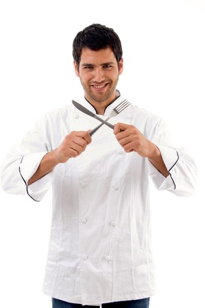 portrait of young male chef holding fork and knife against white background photo