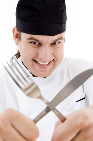 smiling young male chef holding fork and knife on an isolated white background Stock Photo - 3998220