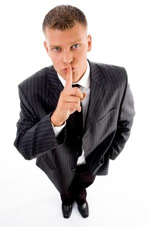guardar silencio: ejecutivo instruyendo a guardar silencio sobre un fondo blanco aisladas Foto de archivo