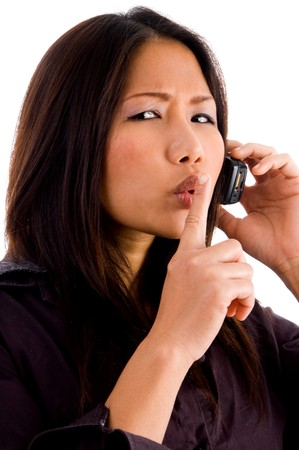 shushing: young corporate woman talking on cell phone and shushing on an isolated background