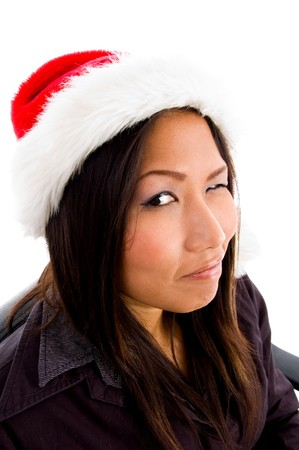 young female in christmas hat winking against white background photo
