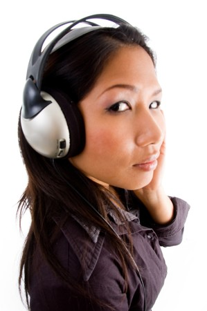 asian female looking at camera while listening to music on an isolated background photo