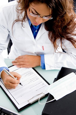 high angle view of young doctor writing prescription in an office photo