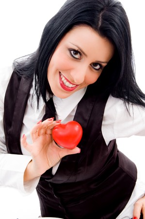 21: woman smiling and holding a small red heart against white background