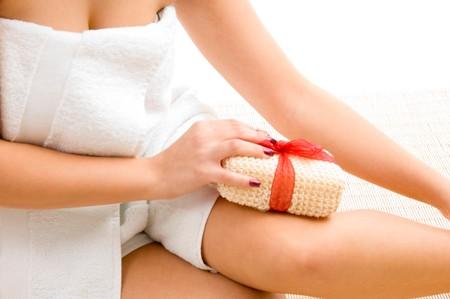 fregando: cerrar la vista de la mujer contra el lavado de la pierna fondo blanco