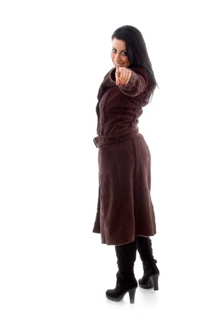 side view of pointing female wearing overcoat against white background photo