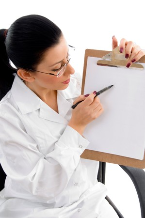side view of female doctor indicating writing pad with white background photo