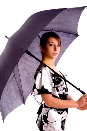 side pose of young woman holding an umbrella against white background photo