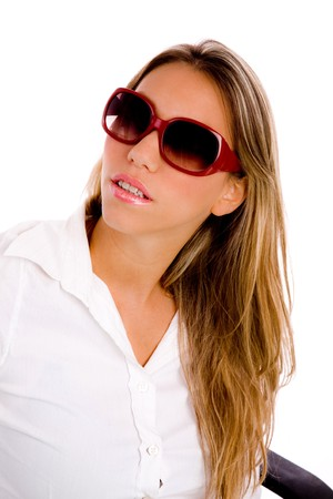 26: portrait of young woman wearing sunglasses with white background