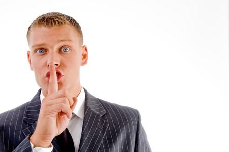 shushing: portrait of executive instructing to keep shushing on an isolated white background