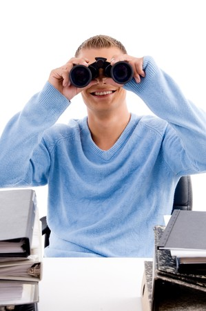 young professional looking through binocular  in an office photo
