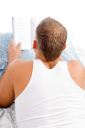man reading book while resting on in bed photo