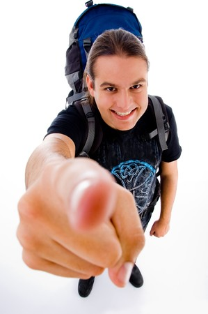 young traveler with bag pack pointing at camera against white background photo