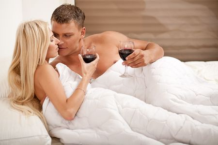 Couple drinking on the bed in bedroom Stock Photo