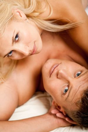 men sex: man and woman in bed looking at camera