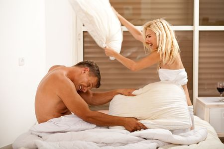 lovers in bed: lovers in bed having a pillow fight Stock Photo