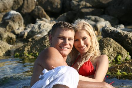 Loving couple at the beach in front of camera photo