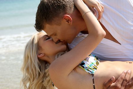 Caucasian couple kissing on the beach