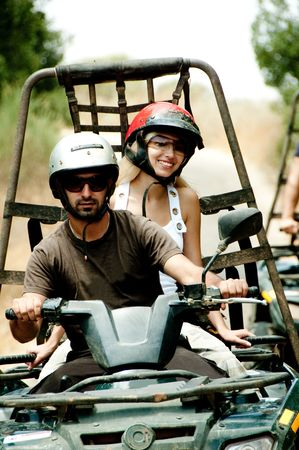 Young man drives the quad as female smiles looking towards camera