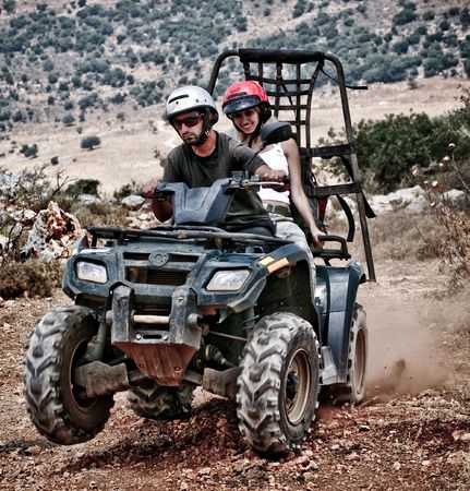 Young couple riding sand buggy and having fun photo