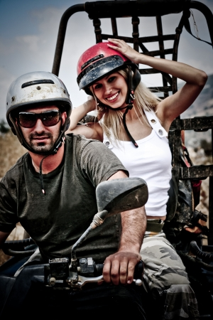Happy young couple on ATV Stock Photo