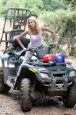 Pretty young lady posing on quadbike photo
