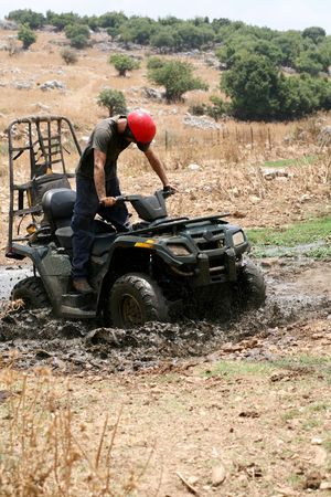 Young man badly stuck in mud with his quadbike