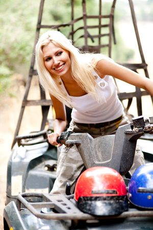 Blonde woman riding quad and looking away with smile on her face photo