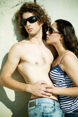 bare chest: Man and woman making love resting on wall