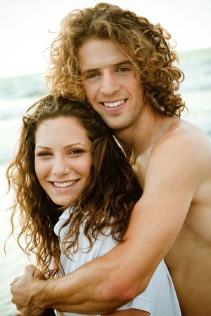 Smiling young couple by the beach photo