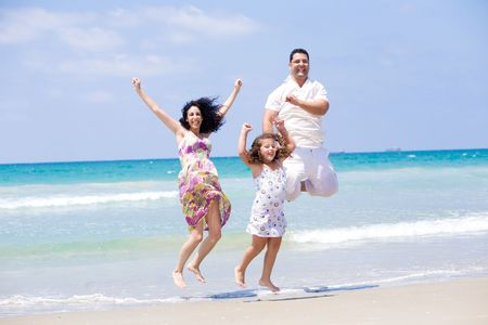 Young family on beach jumping high with daughter Stock Photo - 5419704