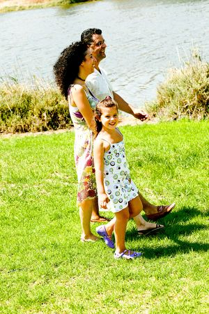tightly: Family walking outdoors holding hands tightly Stock Photo
