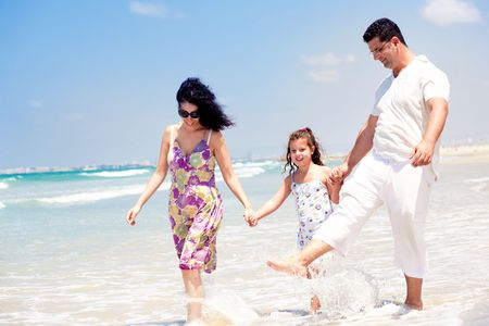 Couple holding daughters hand tightly while walking as man splashes water photo