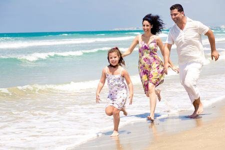 Parents chasing daughter on the beach