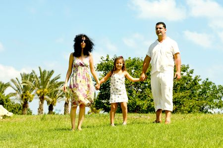 Daughter holding hands of her parents on natural background photo
