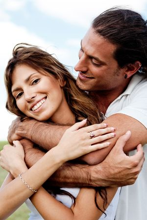 gorgeous woman: Gorgeous female smiling as handsome young man embraces her from back Stock Photo