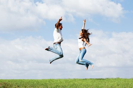 Playful couple jumping high in air