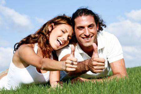 Man and lady showing thumbs-up at camera photo