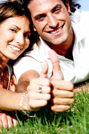 Young couple lazing on sunny day with thumb-s up gesture photo