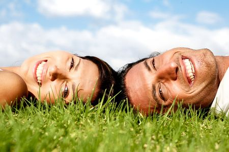 Smiling couple lying on grass and relaxing photo