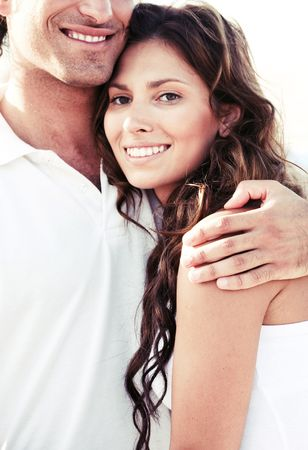 Young man holding lady tightly with arms around her shoulders photo