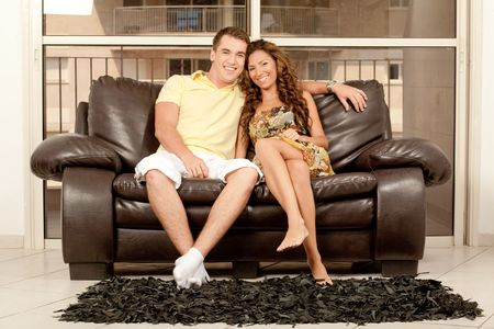 Smiling young couple seated on couch and looking at camera