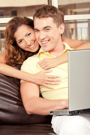 Young woman embracing her man from behind and smiling photo