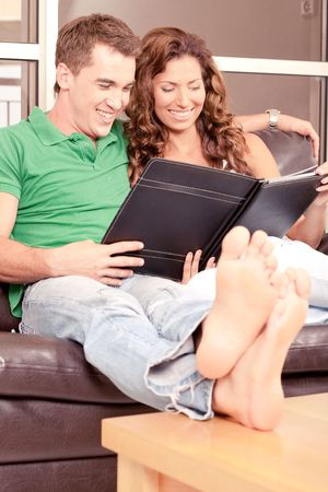 Adorable couple viewing album and smiling photo
