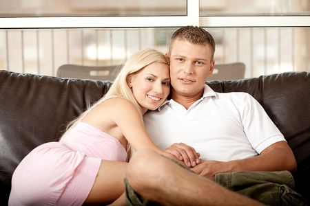 Young guy and lady emracing, while facing camera and relaxing photo