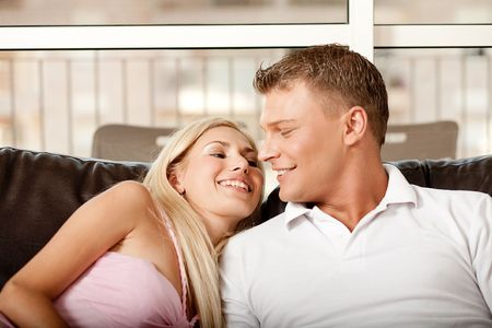 Man and woman relaxing on couch and exchanging words Standard-Bild