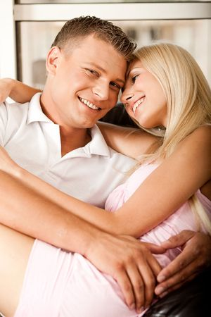 Sexy young lady sitting on mans lap embracing him and smiling photo